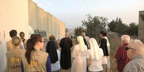 "EAPPI delegates pray by the separation barrier. source: ""church group that sends volunteers to west bank 'witness life under occupation'"" jewish chronicle, may 27, 2016"